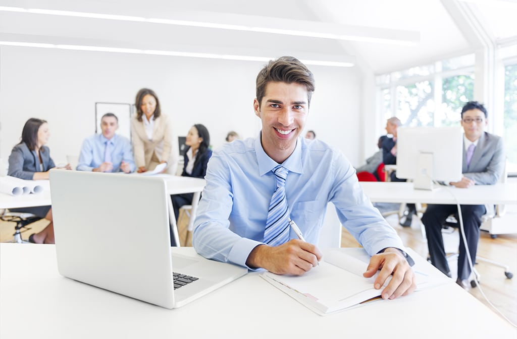 Cheerful Corporate Businessman Working with His Paperworks and Laptop